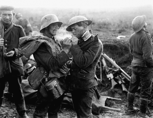 A wounded German soldier lighting a cigarette for a wounded British soldier at a British field hospital during the Battle of Épehy, near the end of the First World War (1918). Photo: Lt. Thomas K. Aitken, British Army photographer/Imperial War Museums.