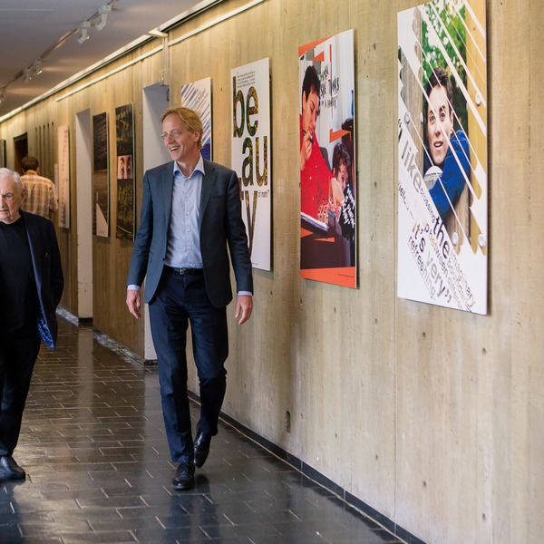 Frank Gehry and Robbert Dijkgraaf converse in a hallway of Simons Hall at IAS