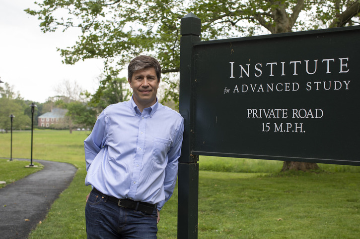 Matias Zaldarriaga stands with the entrance sign at the Institute for Advanced Study