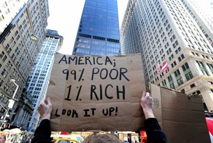 "A demonstrator holds a sign that reads ""America; 99% Poor, 1% Rich. Look it up!"""