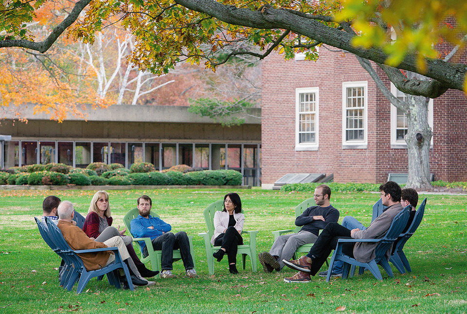 A small group sits on the lawn in discussion