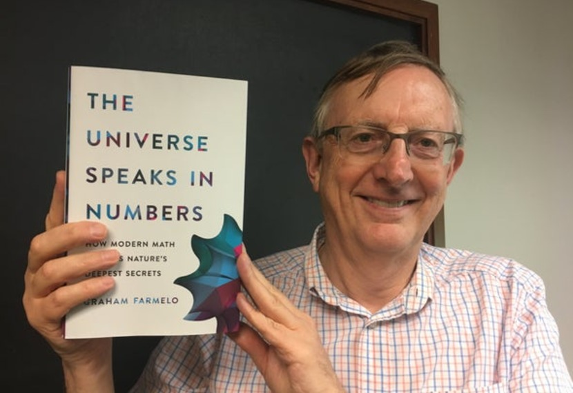 "Graham Farmelo poses with his book ""The Universe Speaks in Numbers"""